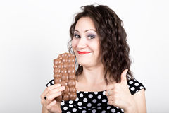 Beautiful young woman eating a chocolate bar, wears a dress with polka dots. expresses different emotions.  Stock Images