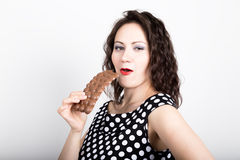 Beautiful young woman eating a chocolate bar, wears a dress with polka dots. expresses different emotions Stock Photo