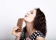 Beautiful young woman eating a chocolate bar, wears a dress with polka dots. expresses different emotions Stock Photos