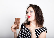 Beautiful young woman eating a chocolate bar, wears a dress with polka dots. expresses different emotions.  Royalty Free Stock Images