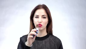 Beautiful young woman eating chocolate isolated over white background. Slow motion stock video footage