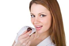Beautiful young woman eating chocolates Stock Photos