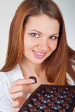 Beautiful young woman eating chocolates Royalty Free Stock Photography