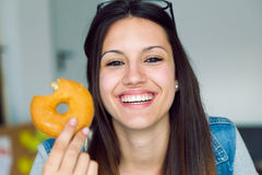 Beautiful young woman eating donuts at home. Stock Photos