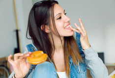Beautiful young woman eating donuts at home. Stock Photo