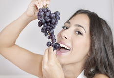 Beautiful young woman eating grapes Stock Photography