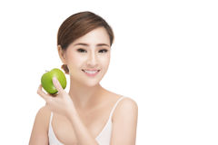 Beautiful young woman eating green apple. With health teeth. Isolated over green background, asian beauty model Stock Photography
