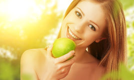 Beautiful young woman eating green apple in the summer on the na Royalty Free Stock Images