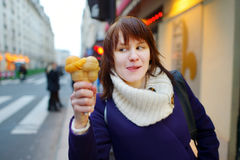 Beautiful young woman eating ice cream outdoors Stock Photography