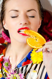 Female eating orange slice over bath background stock photo