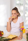 Beautiful young woman eating pineapple Royalty Free Stock Image