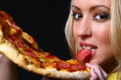Beautiful young woman eating pizza Stock Photos