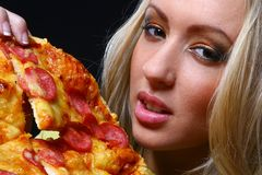 Beautiful young woman eating pizza Stock Images
