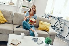 Beautiful young woman. Eating popcorn and smiling while watching TV on the sofa at home stock image