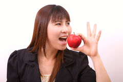 Beautiful young woman eating red apple Stock Image