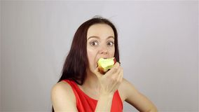 Beautiful young woman eating a red apple stock video footage
