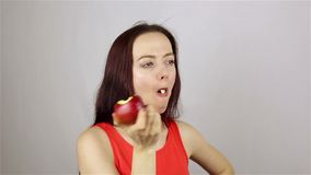 Beautiful young woman eating a red apple stock video