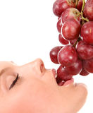 Beautiful young woman eating red grapes Stock Photo