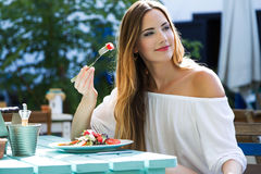 Beautiful young woman eating salad in the home garden. Stock Photo