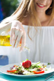 Beautiful young woman eating salad in the home garden. Stock Photos