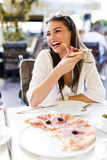 Beautiful young woman eating a slice of pizza in a restaurant. Outdoors royalty free stock photo