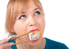 Beautiful young woman eating sushi with chopsticks Stock Image