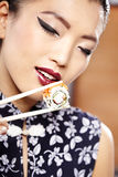 Beautiful young woman eating sushi. Stock Photography