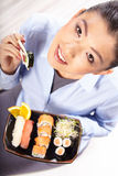 Beautiful young woman eating sushi. Royalty Free Stock Photo