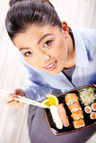 Beautiful young woman eating sushi. Stock Image