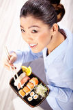 Beautiful young woman eating sushi. Stock Images