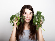 Beautiful young woman eating an vegetables. choice, parsley or dill. healthy food - strong teeth concept Stock Photo