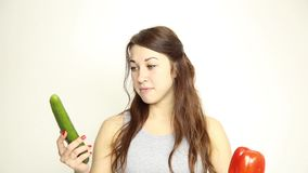 Beautiful young woman eating an vegetables. holding cucumber and red pepper. healthy food - healthy body concept