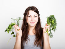 Beautiful young woman eating an vegetables. holding dill and parsley. healthy food - healthy body concept Stock Photography