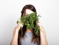 Beautiful young woman eating an vegetables. holding dill and parsley. healthy food - healthy body concept Royalty Free Stock Photography