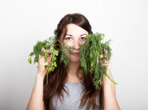 Beautiful young woman eating an vegetables. holding dill and parsley. healthy food - healthy body concept Royalty Free Stock Images
