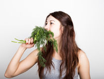 Beautiful young woman eating an vegetables. holding dill and parsley. healthy food - healthy body concept Stock Photos
