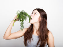 Beautiful young woman eating an vegetables. holding dill and parsley. healthy food - healthy body concept Royalty Free Stock Photo
