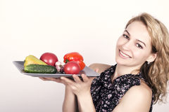 Beautiful young woman eating an vegetables. holding a plate with vegetables, red pepper, tomato, cucumber. healthy food Stock Image