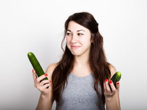 Beautiful young woman eating an vegetables. selection, small or big cucumber. healthy food - strong teeth concept Royalty Free Stock Images