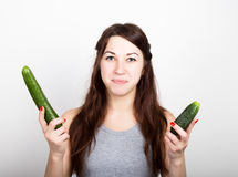 Beautiful young woman eating an vegetables. selection, small or big cucumber. healthy food - strong teeth concept Stock Photography