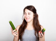 Beautiful young woman eating an vegetables. selection, small or big cucumber. healthy food - strong teeth concept Stock Images