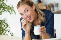 Beautiful young woman eating yogurt at home. Stock Photography