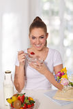 Beautiful young woman eating yogurt with strawberry Stock Photos