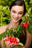 Beautiful young woman eats cherry on plantation Stock Photos