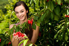 Beautiful young woman eats cherry on plantation Royalty Free Stock Photography