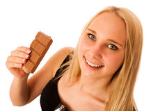 Beautiful young woman eats chocolate isolated over white backgro Stock Images