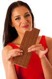 Beautiful young woman eats chocolate isolated over white backgro Royalty Free Stock Photography