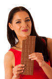 Beautiful young woman eats chocolate isolated over white backgro Royalty Free Stock Images