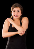 Beautiful young woman with elbow pain, in black background.  Royalty Free Stock Image