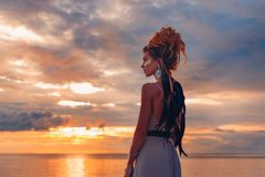 Beautiful young woman in elegant dress on the beach at sunset stock image